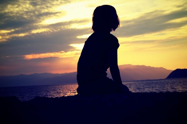夕闇の中を一人座る女性